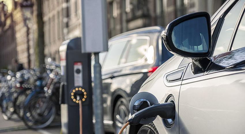 Seitenansicht eines Elektroautos an einer Ladestation