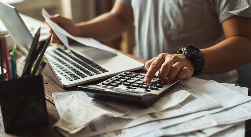 Mann sitzt vor seinem Laptop und tippt Rechnungen in einen Taschenrechner