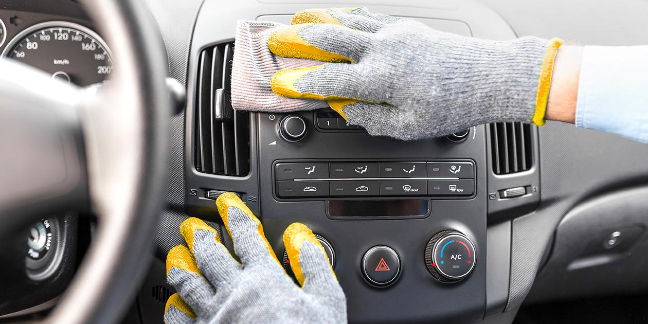 Hand mit Handschuh, die Auto putzt.