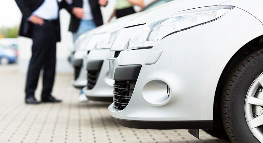 Drei weiße Autos in einer Reihe geparkt.