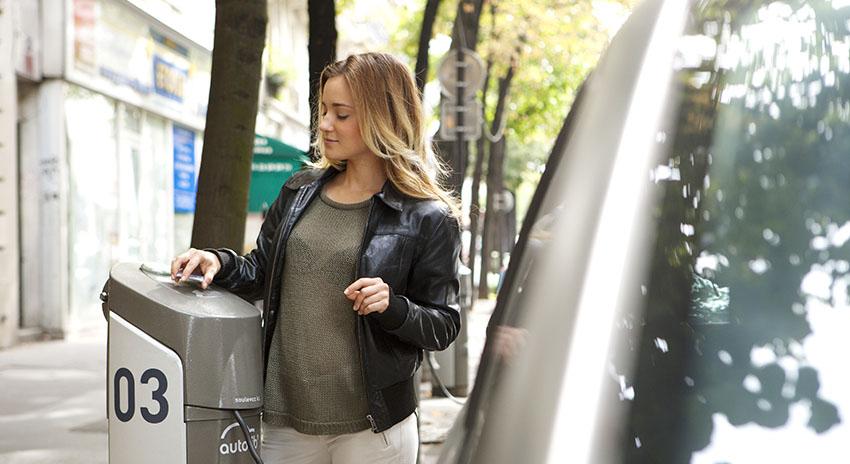Frau an einer Ladestation für E-Fahrzeuge