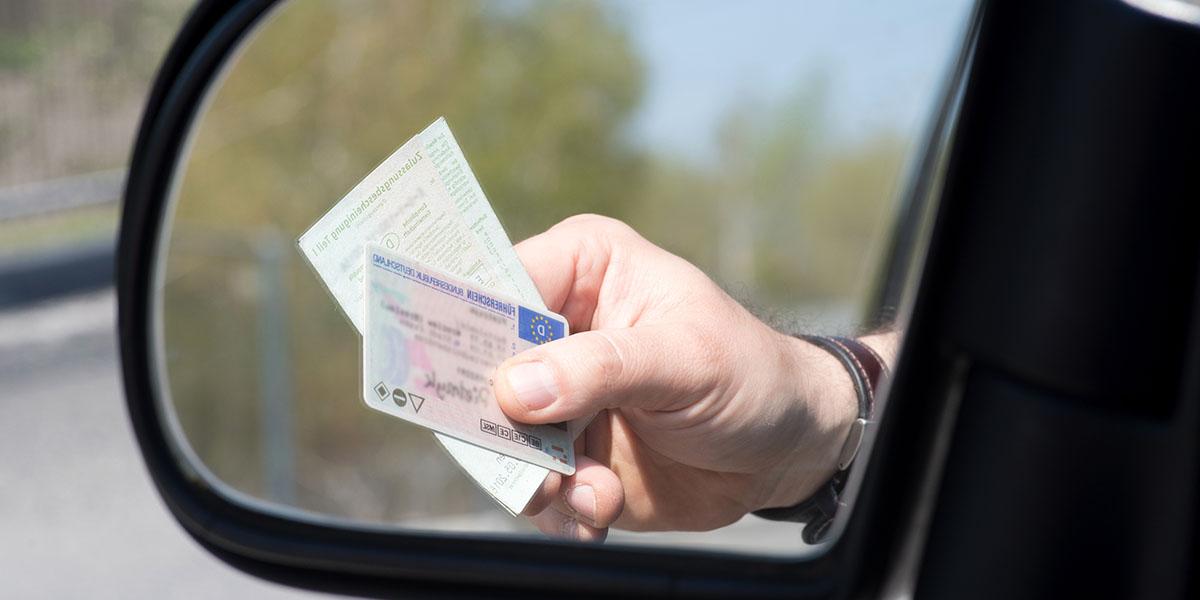 Hand hält Führerschein aus dem Auto