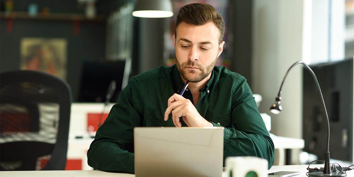 Mann am Schreibtisch mit Laptop