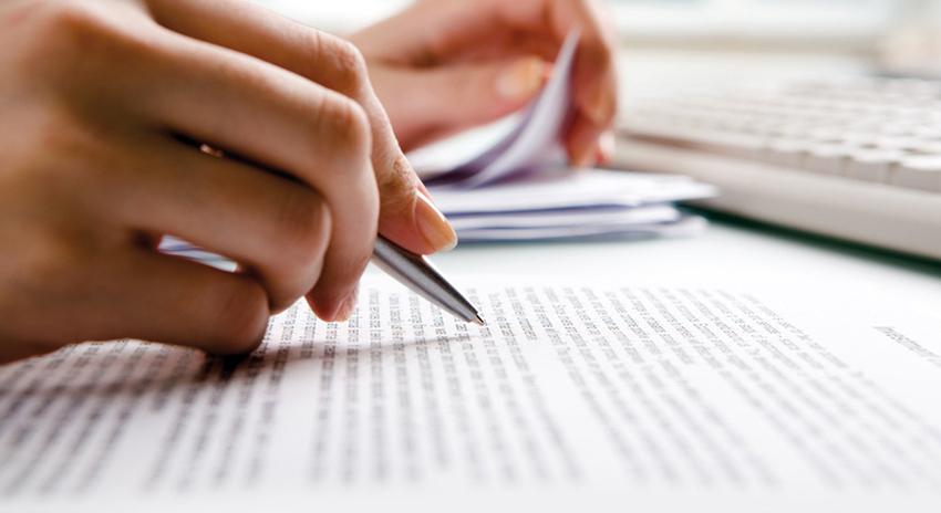 Hand hält Kugelschreiber über Unterlagen