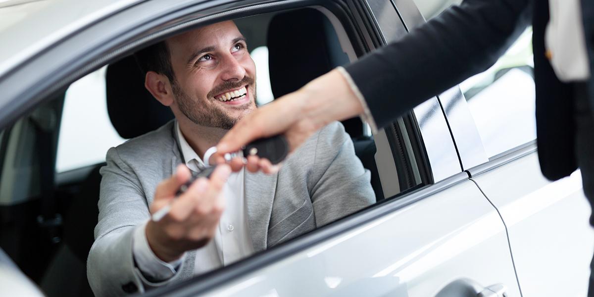 Mann sitzt im Auto und erhält Schlüssel