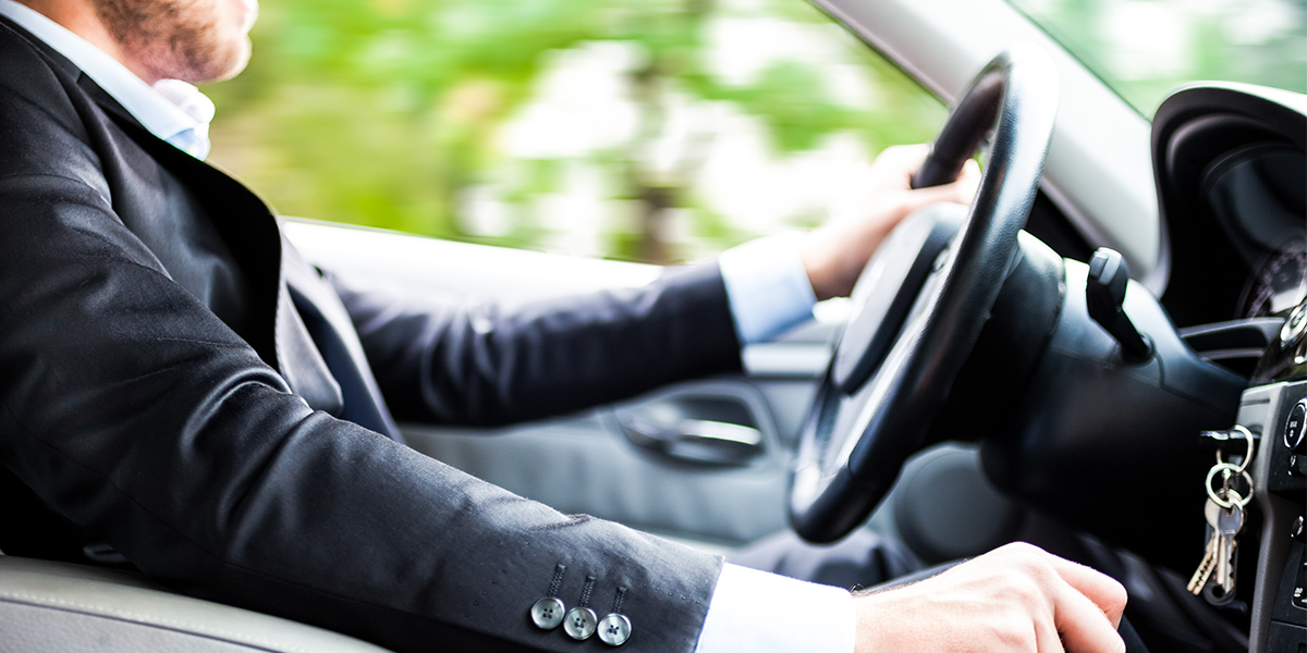 Man in a suit sits at the wheel and drives a car