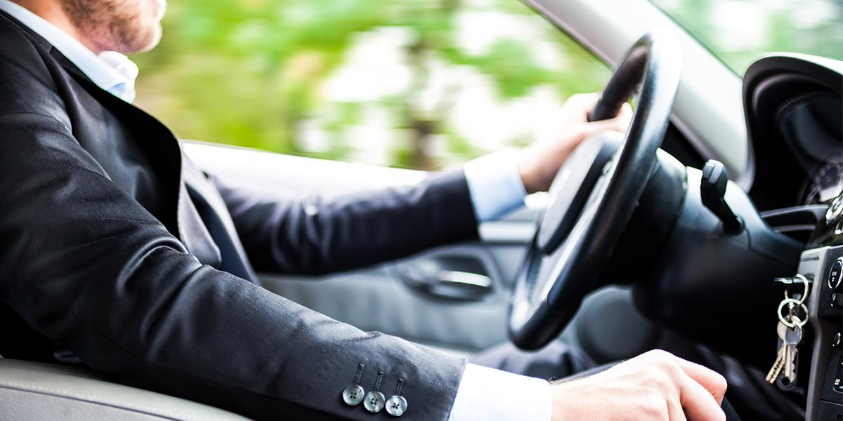 Mann im Anzug sitzt am Steuer und fährt Auto