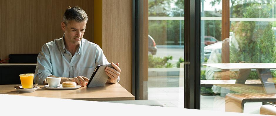 Mann an einem Tisch mit Tablet