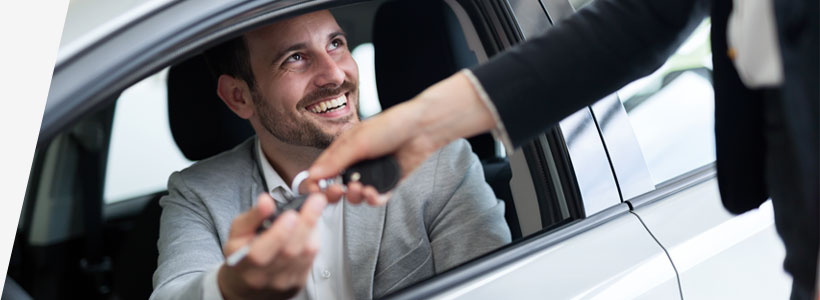 smiling business man receives keys for car