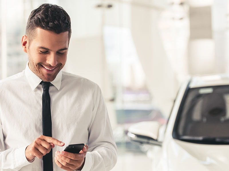 Man in front of business car with smartphone