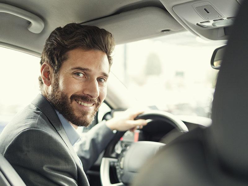 Dienstwagenfahrer, der am Steuer sitzt und über die Schulter schaut.