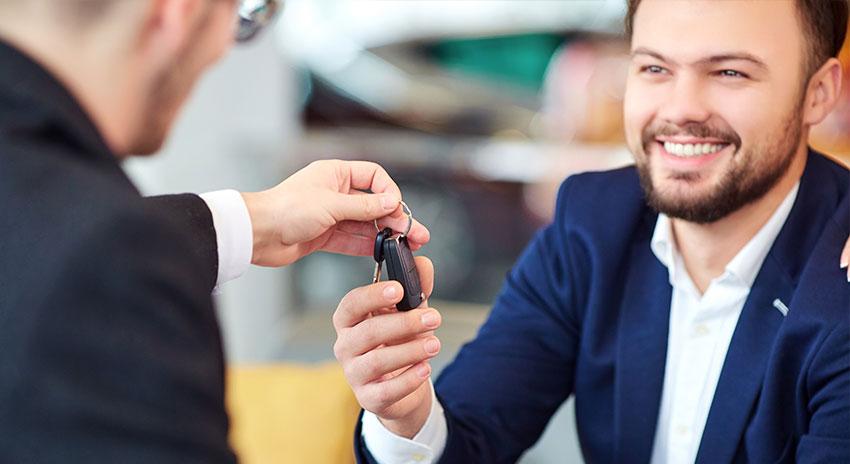 Dienstwagenfahrer, der einen Autoschlüssel überreicht bekommt